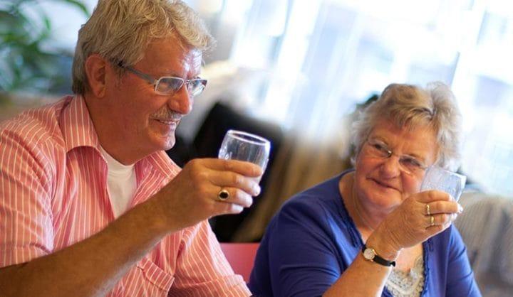 Oudere dame en heer met een glas drinken in hun hand