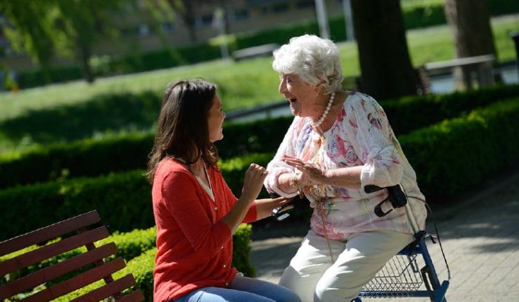 Zorg in Nederland: Dame maakt, zitten op rollator een praatje met jonge vrouw.