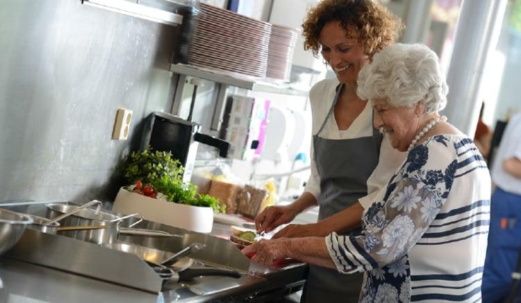 Samen koken: vrouw helpt oudere dame in de keuken