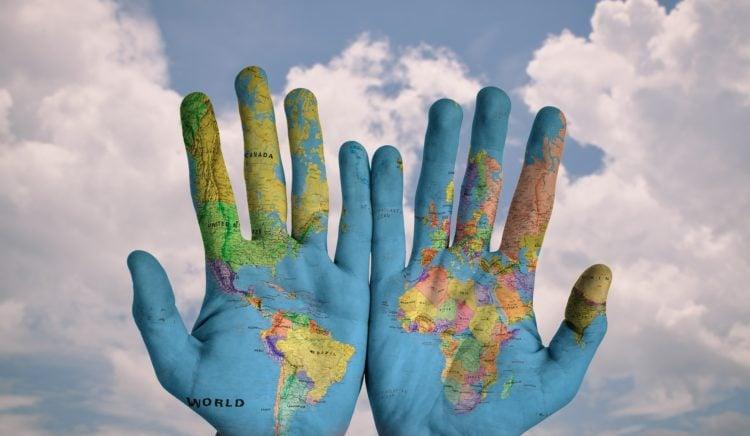 Duurzaamheid (symbolisch): blauw geschilderde handen met de wereldkaart erop. Met in de achtergrond een blauwe lucht met wolken.