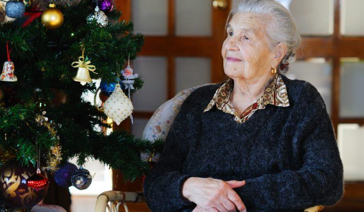 Oudere dame eenzaam bij kerstboom